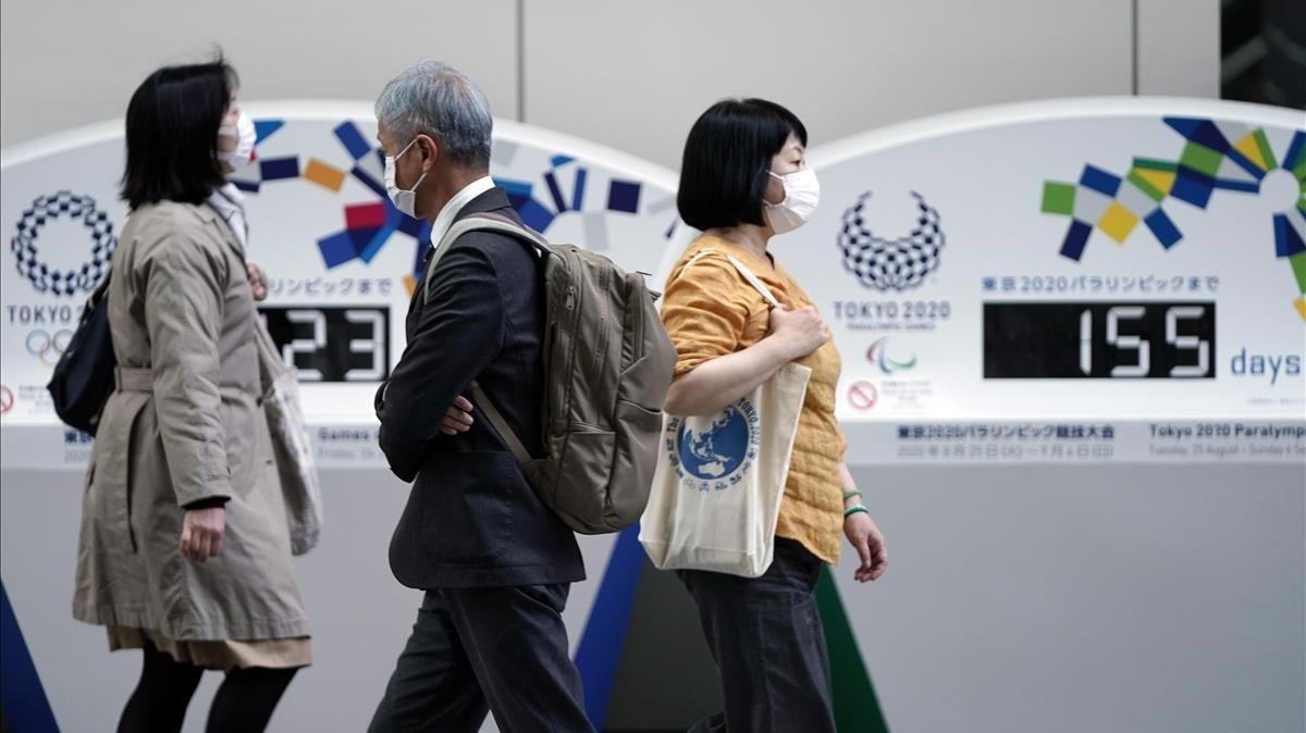 Un grupo de personas pasea en Tokio ante un marcador que indica los supuestos días que faltan para el inicio de los Juegos.