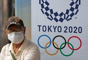 Un habiante de Bangkok, en Tailanda, con mascarilla y frente a un cartel de los Juegos.