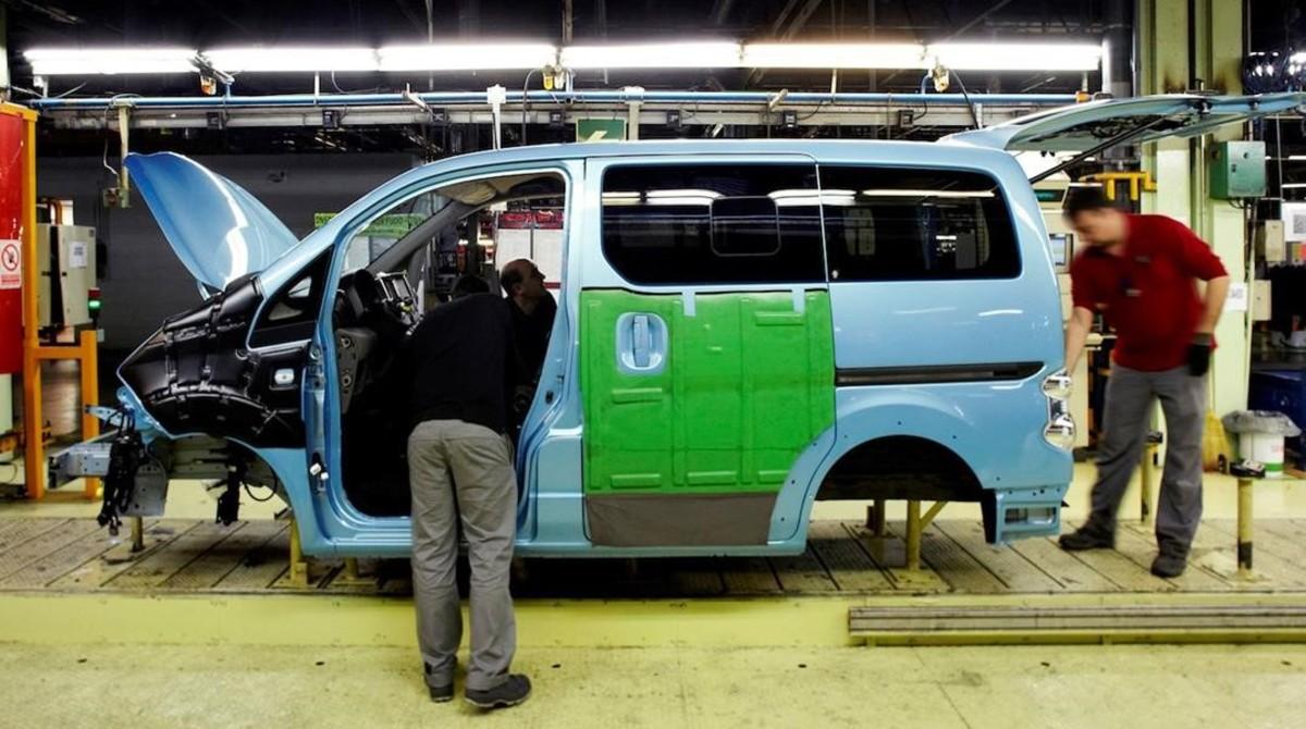 Trabajadores en la fábrica de Nissan en la Zona Franca de Barcelona en el montaje de la furgoneta eléctrica e-NV200.