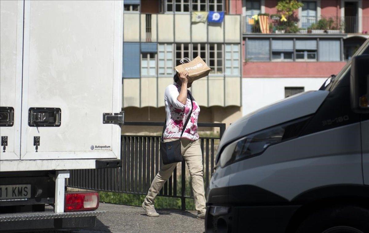 Una mujer se protege del calor en Girona.