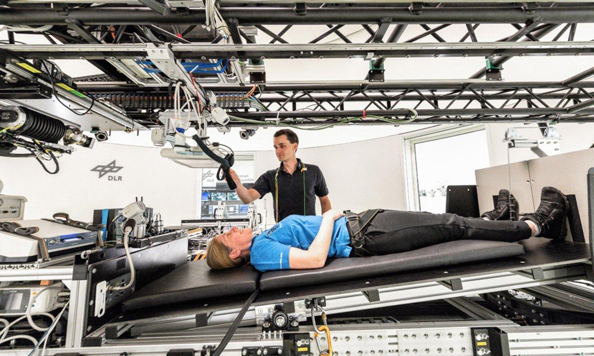 Una mujer tumbada en una cama centrífuga, en el Centro Aeroespacial Alemán en Colonia.