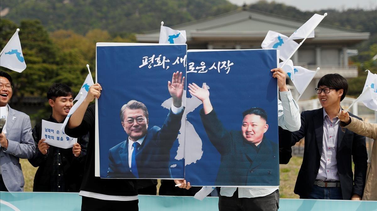 Estudiantes favorables a la reunificación exhiben imágenes de los dos presidentes en una concentración en Seúl.