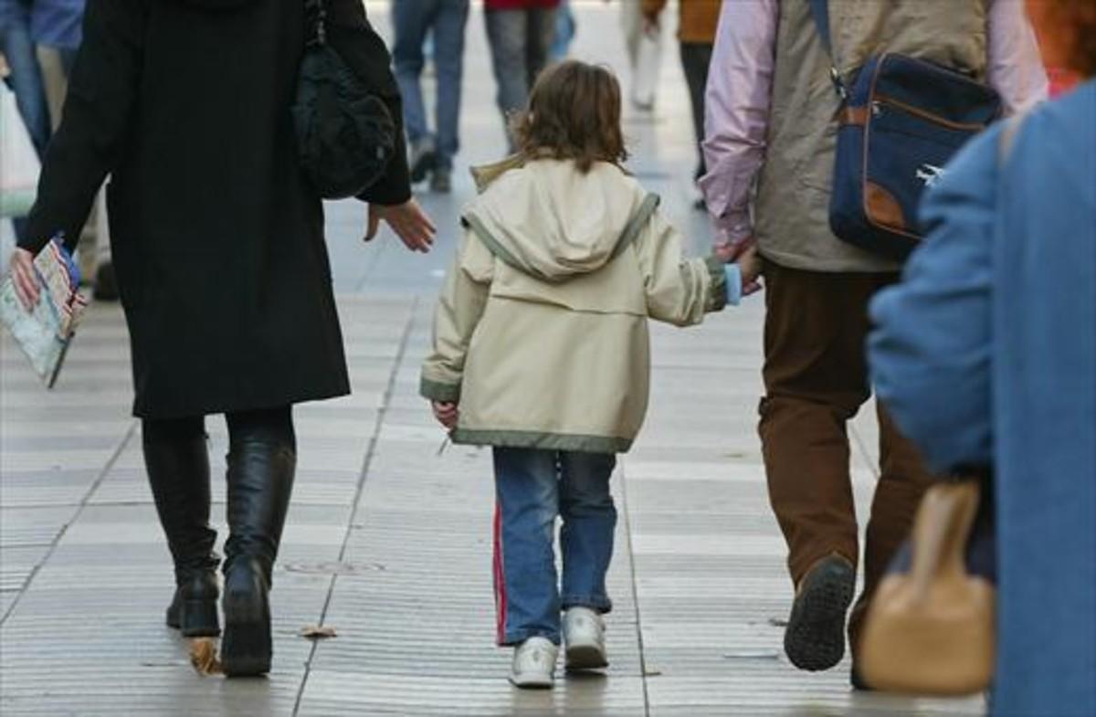Unos padres pasean con su hijo, cogidos de la mano.