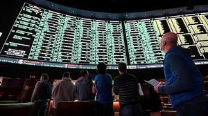Usuarios deuna casa de apuestas de Las Vegas observan el panel de opcionesdisponiblepara un partido de fútbol americano entre los Atlanta Falcons y los New England Patriots.