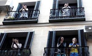 Vecinos del barrio de Lavapiés, en Madrid, aplauden a los sanitarios desde sus balcones.
