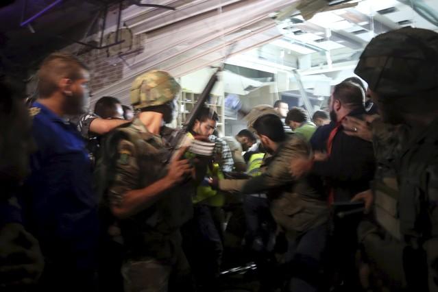 Vecinos, soldados y miembros de la Defensa Civil inspeccionan el daño causado por las explosiones.