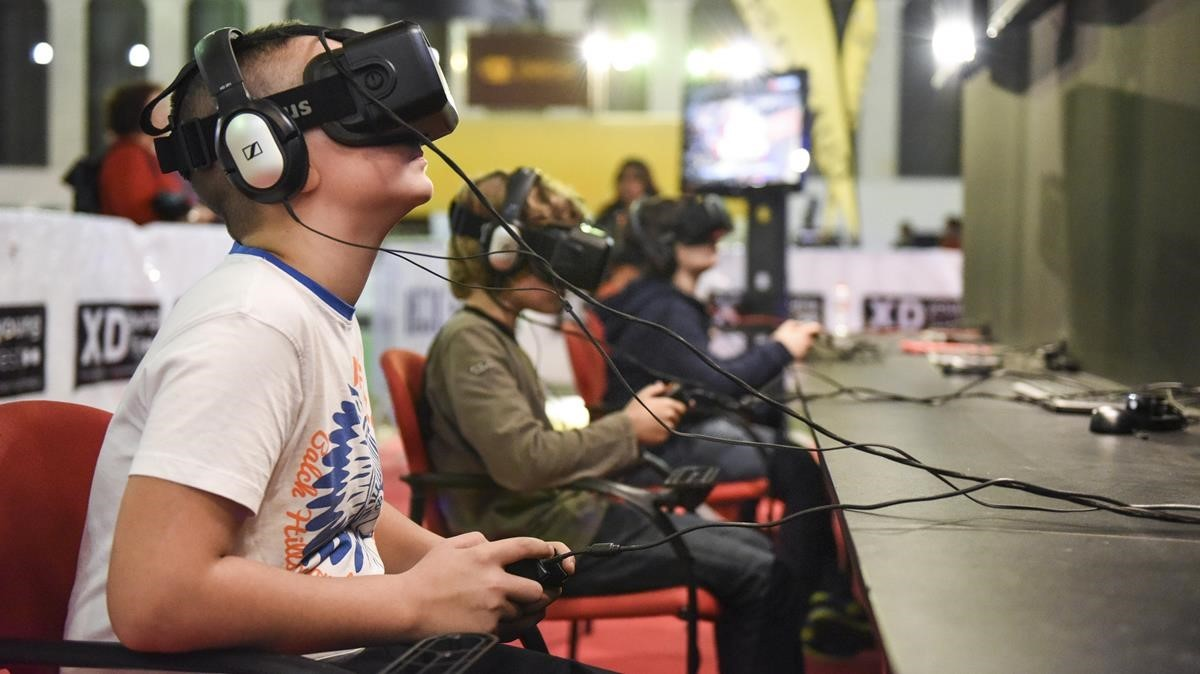 Unos adolescentes juegan a videojuegos en 3D en una feria de Barcelona. / Adriana Domínguez