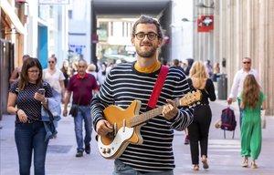 Borja Catanesi, músico callejero, con su guitarra en València