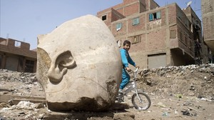 ealos37617847 a boy rides his his bicycle past a recently discovered statu170310132531
