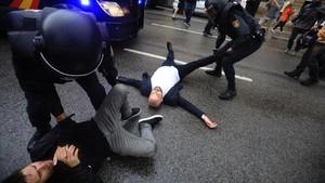 Agentes policiales actúan contra quienes impiden el paso de la Policía Nacional tras la carga en la escuela Ramon Llull, el 1-O.