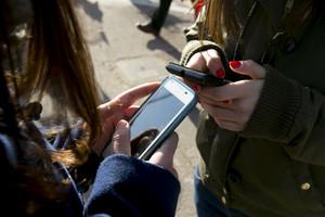 Jóvenes utilizando el móvil a la salida de su instituto.