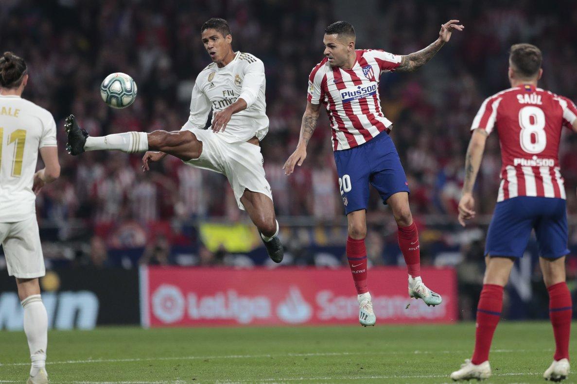 El madridista Varane (i) golpea un balón en el partido ante el Atlético de Madrid.