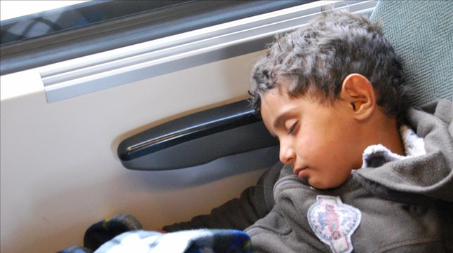 Un niño duerme en el tren con destino a Austria.