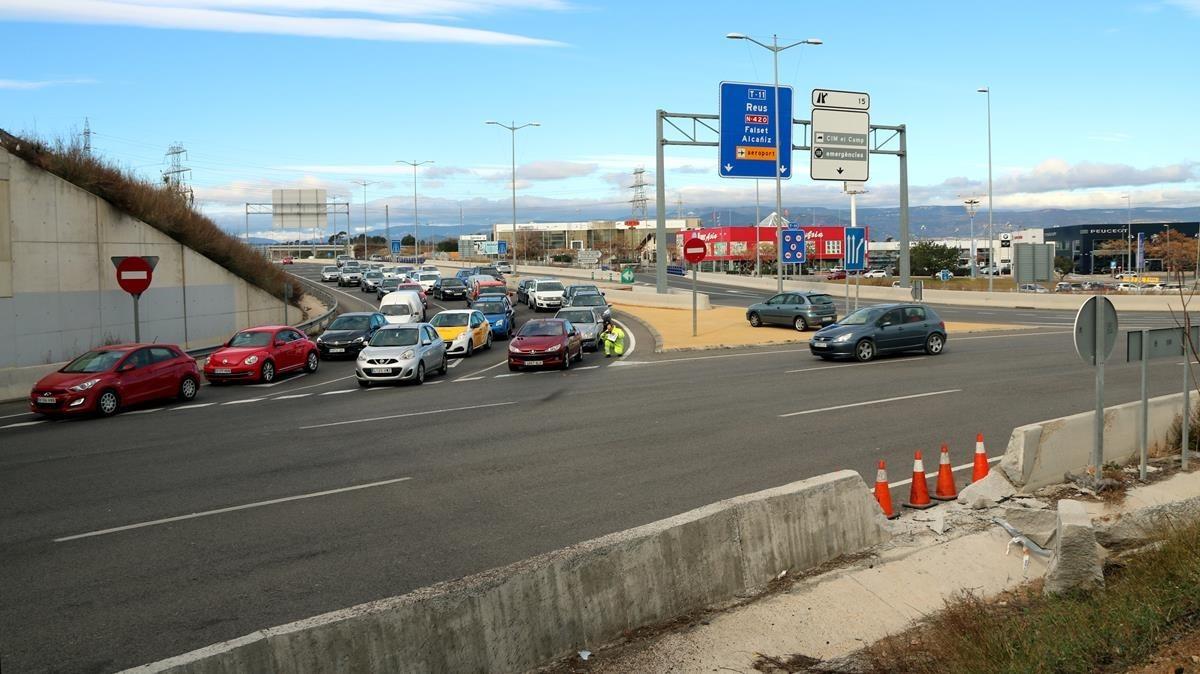 Accidente en Les Gavarres en la T-11 a Tarragona con retenciones de vehículos y la señal del impacto destrozada por un vehículo.