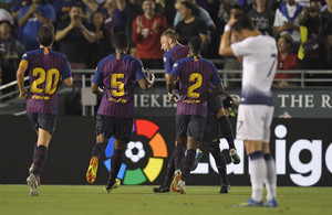 Barcelona midfielder Arthur, center, celebrates his goal with teammates midfielder Sergi Roberto, left, midfielder Marlon Santos, second from left, and defender Nelson Semedo, second from right, as Tottenham forward Son Heung-Min wipes his head during the first half of an International Champions Cup tournament soccer match Saturday, July 28, 2018, in Pasadena, Calif. (AP Photo/Mark J. Terrill)