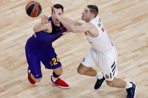 El azulgrana Kuric pelea por un balón con el madridista Causeur