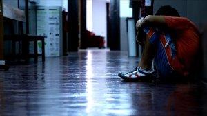 Un niño, víctima de acoso escolar, se tapa la cara en el pasillo de un colegio.