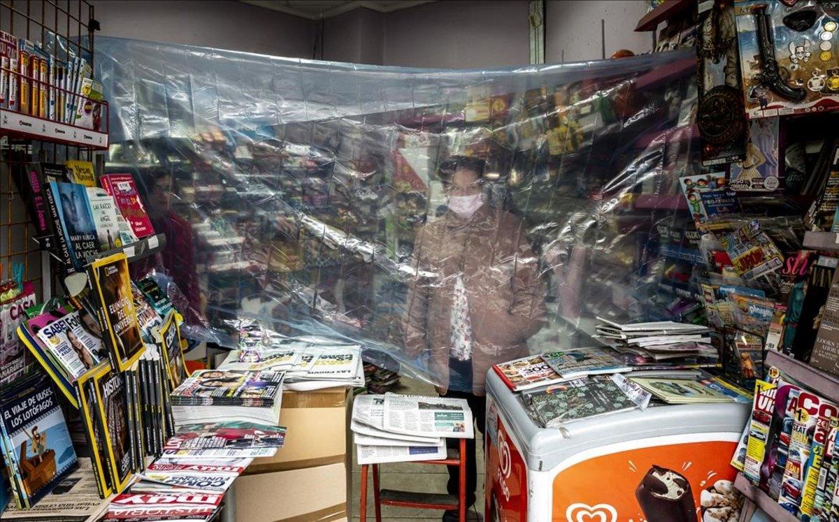 Una kioskera se protege con un plástico en Valencia.