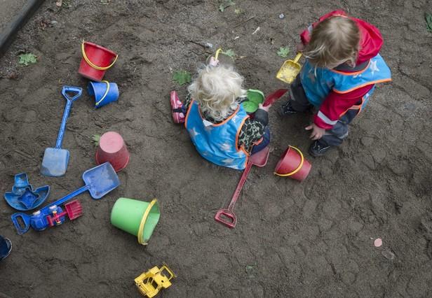 Dos niños juegan con la arena en el patio de una guardería.