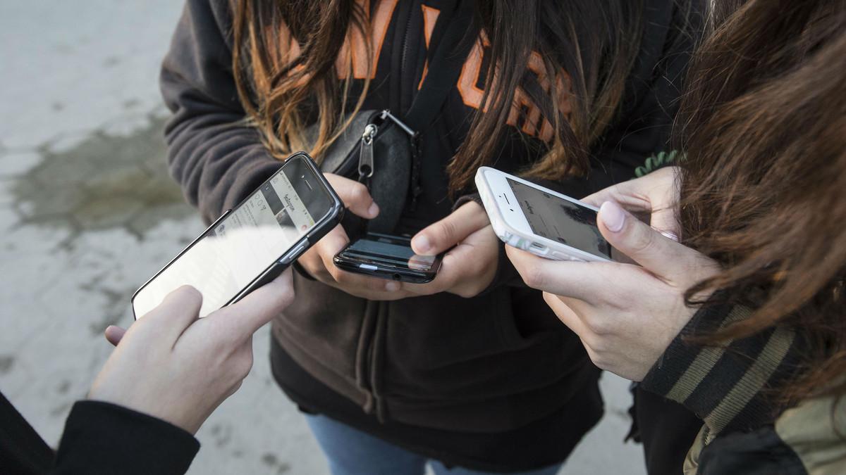 Un grupo de menores consulta su teléfono móvil.