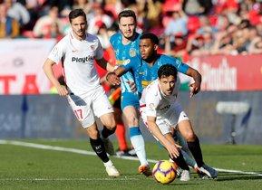 El futbolista del Sevilla Jesús Navas (d) se lleva un balón ante el francés Lemar (Atlético).