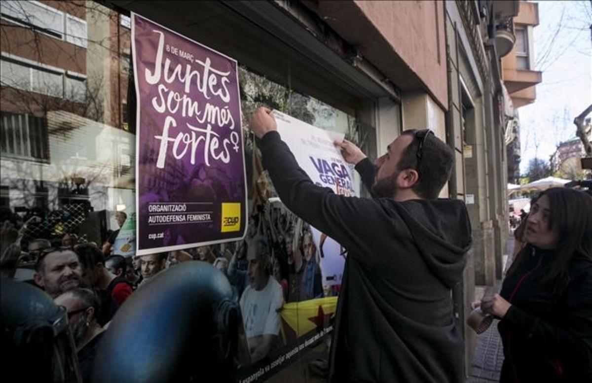 Un militante cuelga un cartel en la sede de la CUP en Barcelona.