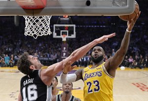 Los Angeles Lakers forward LeBron James, right, shoots as San Antonio Spurs center Pau Gasol, of Spain, defends during the second half of an NBA basketball game Monday, Oct. 22, 2018, in Los Angeles. The Spurs won 143-142. (AP Photo/Mark J. Terrill)