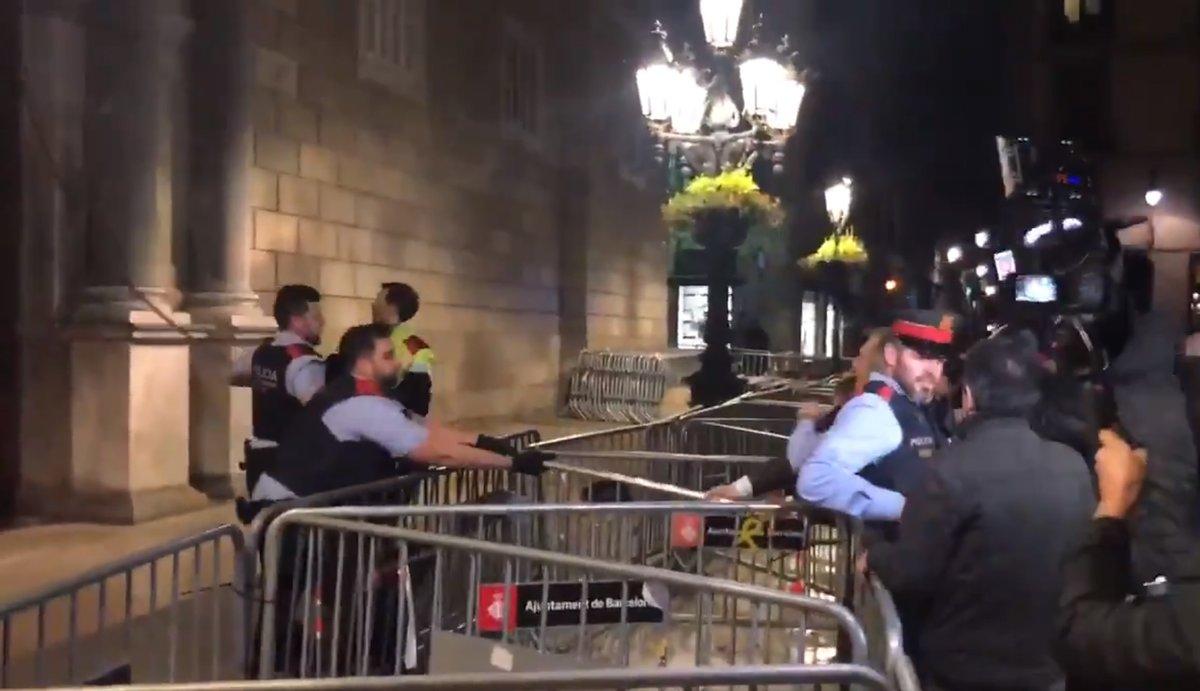 Los Mossos impiden que un grupo de personas retiren con un palo el lazo amarillo de la fachada de la Generalitat.