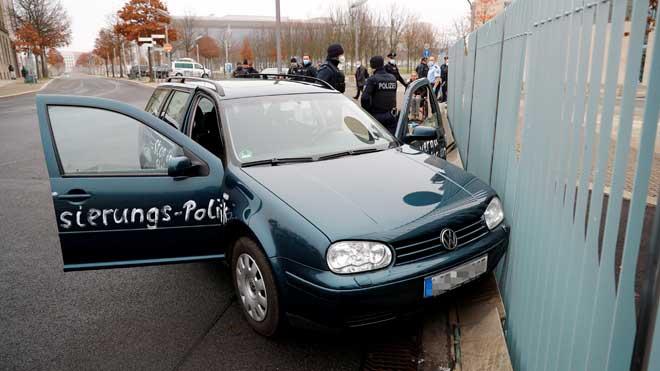Un cotxe amb pintades antiglobalització s'encasta a l'oficina de Merkel