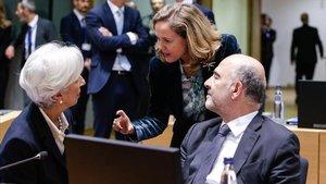 La ministra Nadia Calviño (de pie) conversa con la presidenta del BCE, Christine Lagarde, y el comisario europeo de Asuntos Económicos, Pierre Moscovici, en Bruselas.