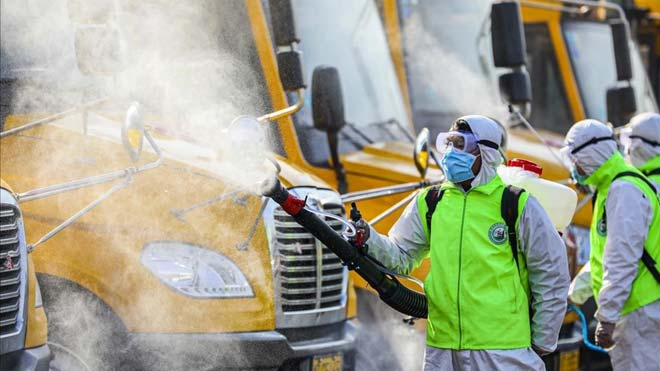 Moncloa aclara que las indicaciones sobre el coronavirus las marca Sanidad. En la foto,Voluntarios desinfectan autobuses escolares en Tengzhou, China.