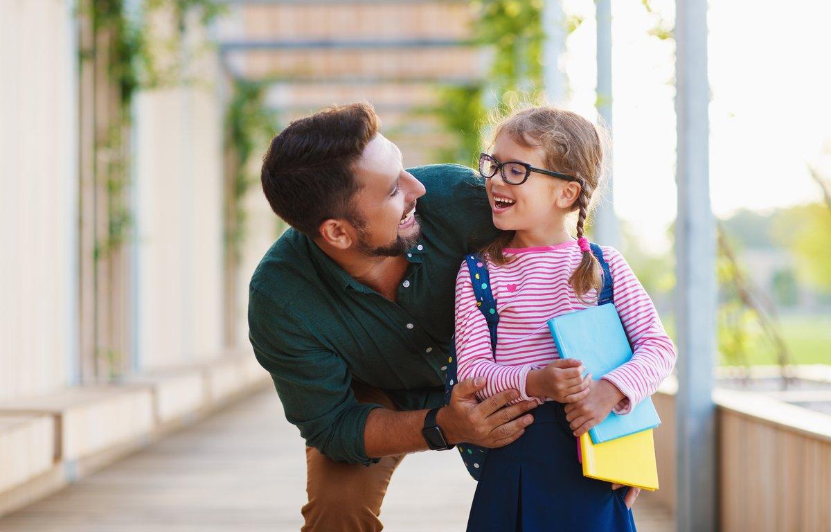 Un padre con su hija a la salida del colegio.