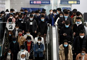 People wearing face masks stand on an escalator inside a subway station during morning rush hour in Beijing, as the spread of the novel coronavirus disease (COVID-19) continues in the country, in China April 7, 2020. REUTERS/Tingshu Wang REFILE - CORRECTING DESCRIPTION OF ESCALATOR