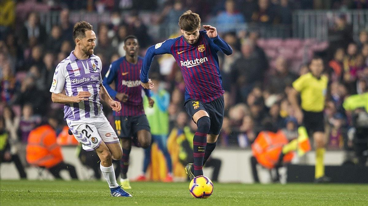 Piqué se incorpora al ataque ante Michel, el jugador del Valladolid, en el Camp Nou.
