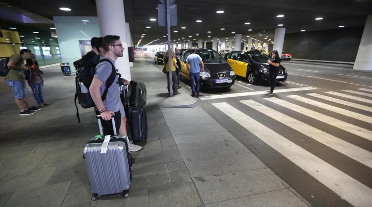 Unos pasajeros se hallan sin taxi para acceder al centro de Barcelona.