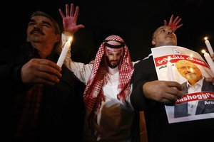 An activist  wearing a mask depicting Saudi Crown Prince Mohammed bin Salman  holds up his hands  painted with fake blood as he protests the killing of Saudi journalist Jamal Khashoggi  during a candlelight vigil outside Saudi Arabia s consulate in Istanbul.  AP Photo Emrah Gurel
