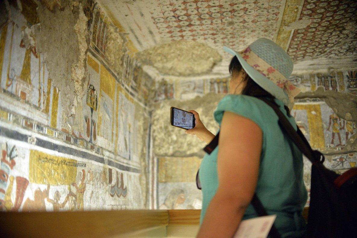 Una mujer fotografía el interior de una de las tumbas restauradasen Dra Abu al Naga, en Luxor.