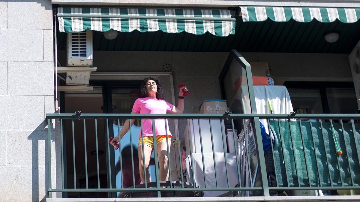 Una mujer hace ejercicio en el balcón de su casa en Ourense, este domingo.