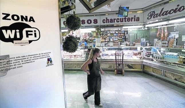 Una mujer pasa ante una zona wifi en el mercado de Antón Martín de Madrid.