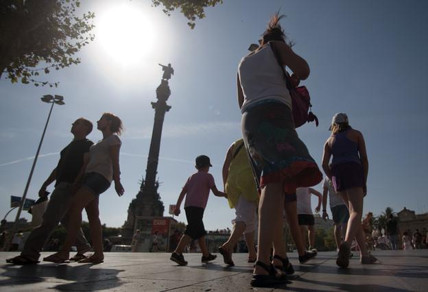 Una turista fotografía el monumento de Colón.