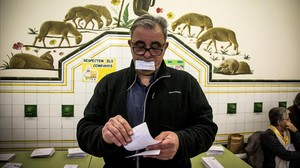 Un hombre recoge una papeleta electoral durante los comicios catalanes del pasado 21 de diciembre.