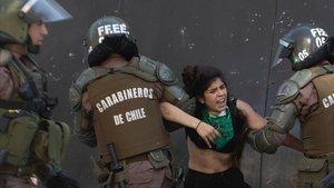 Unos carabineros se llevan detenida a una joven durante una protesta, este jueves, en Santiago de Chile.