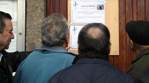 Vecinos de los fallecidos observan la esquela de los ancianos.