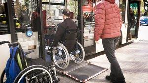 Un voluntario de la Fundació TMB ayuda a una persona en silla de ruedas, el verano pasado.