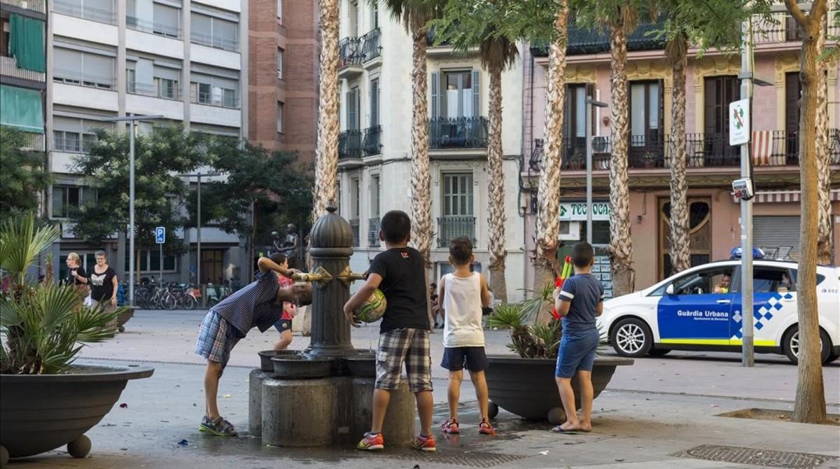 Niños con la pelota bajo el brazo en la plaza de Navas tras la llegada de la Guardia Urbana.