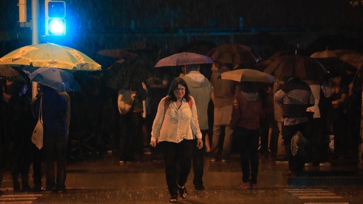 Gente bajo la lluvia en elColegio La Llacuna de Poblenou.