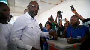 El candidato presidencial y exfutbolista George Weah deposita su voto.