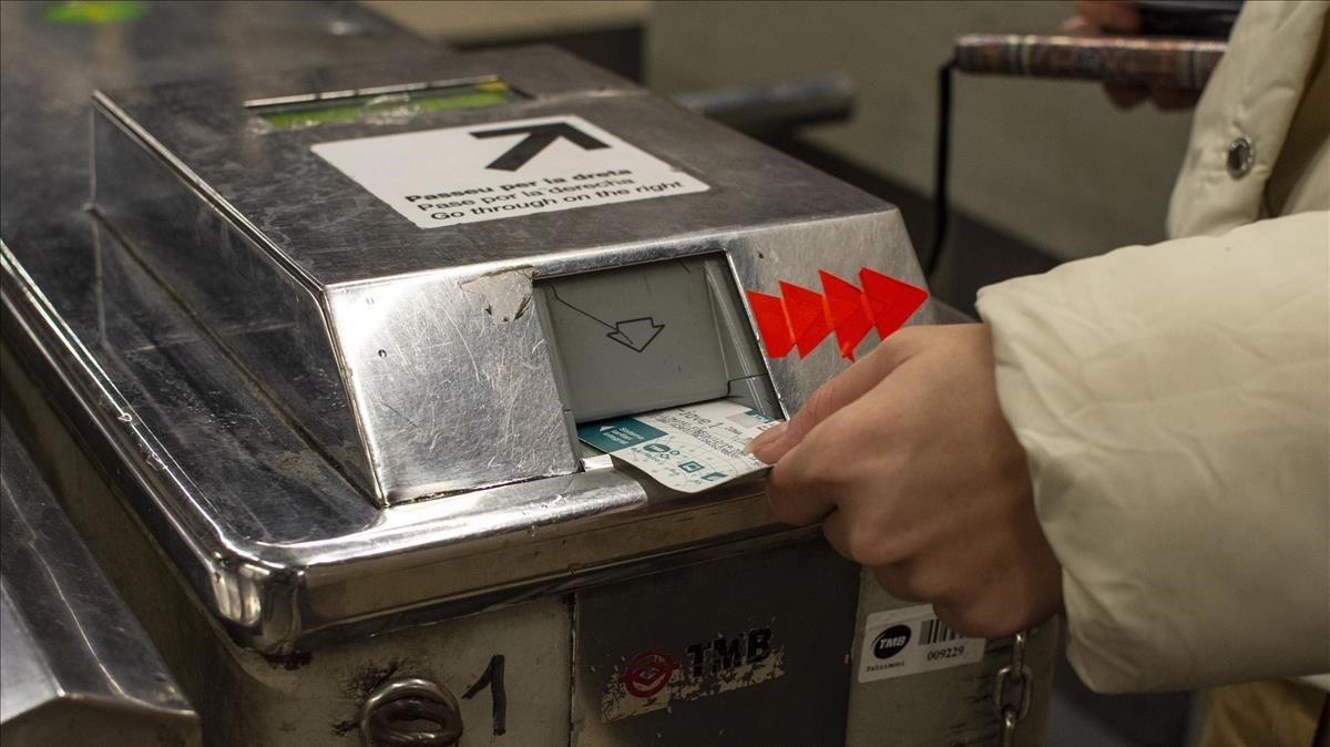 Una usuaria introduce una tarjeta en una máquina de acceso al metro de Barcelona.