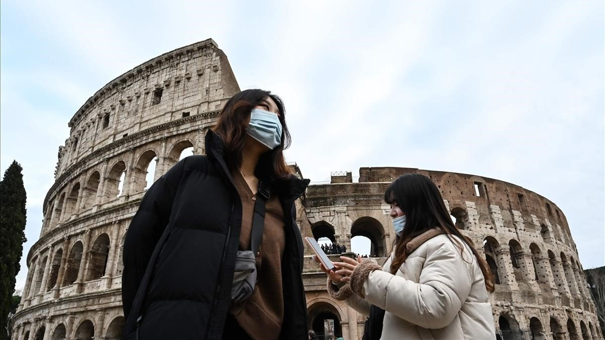 Turistas con mascarillas junto al Coliseo de Roma.