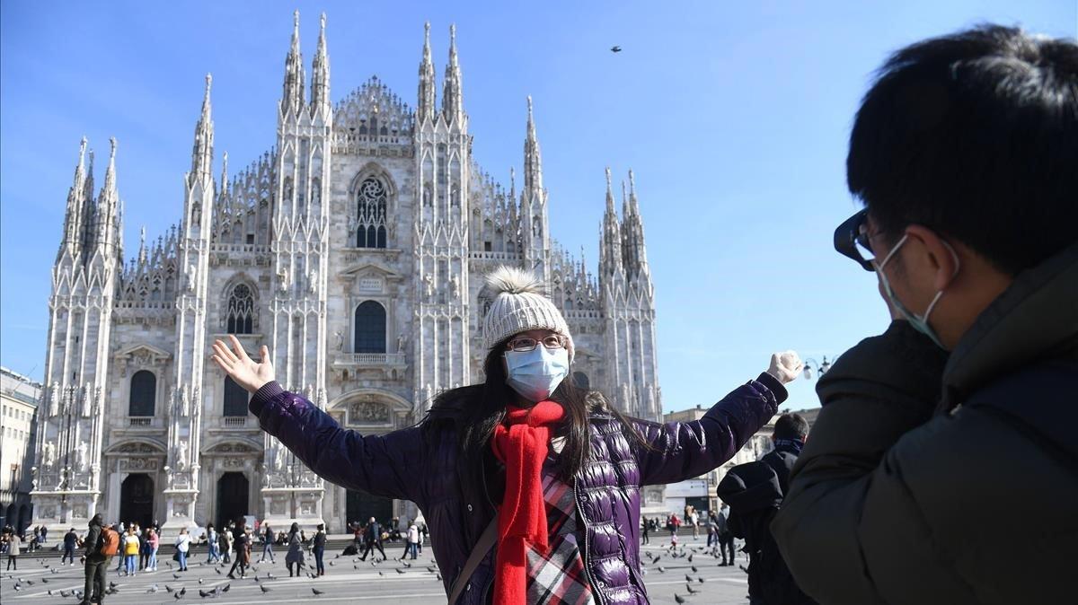 Una turista de Taiwán con mascarilla se fotografía ante el Duomo de Milán.